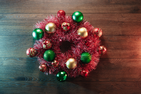 Christmas wreath of red garlands and Christmas toys on the background of a wooden table. Merry Christmas and happy holidays. View from above.