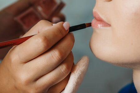 A closeup of delicate woman's lips while visagiste holds a pencil behind her face Stock Photo