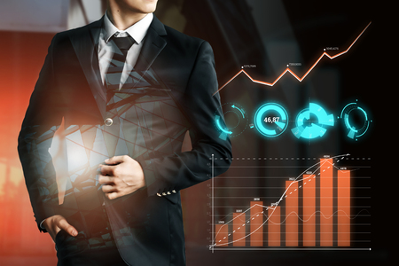 A businessman in a dark suit looks at the hologram graphics, business growth, a positive trend. Dark background. Mixed media