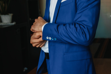 A man buttoning a blue jacket