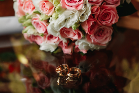Wedding rings with bridal bouquet lying on the morning of the bride.