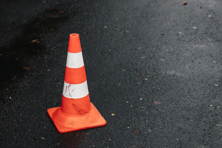 Traffic cone, with white and orange stripes on gray asphalt, copy space Banque d'images