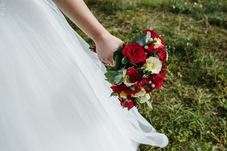 Close up of a bride holding a wedding bouquet with red and white roses. Reklamní fotografie - 122721643