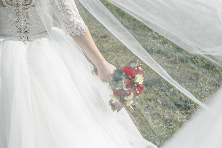 Close up of a bride holding a wedding bouquet with red and white roses. Фото со стока