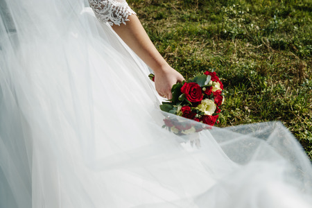 Close up of a bride holding a wedding bouquet with red and white roses. Zdjęcie Seryjne