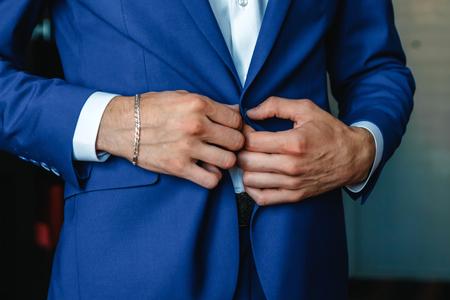 Ein Mann knöpft sich eine blaue Jacke zu Standard-Bild