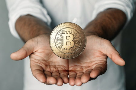 Gold coin Bitcoin in the hand. The concept of crypto currency. Blockchain technology. Imagens - 122720077