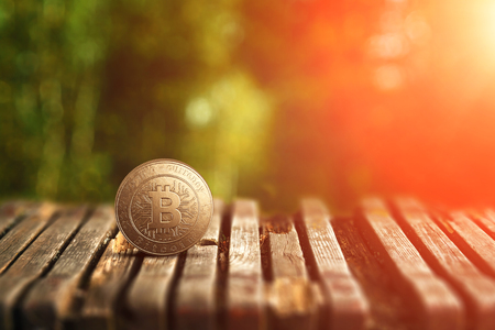 Gold coin Bitcoin on a wooden table on a background of blurred green nature. The concept of crypto currency. Blockchain technology. Imagens - 122720037