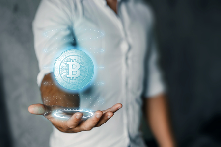 A businessman is holding a bitcoin icon, business, new technologies in his hand. The concept of crypto currency. Blockchain technology. Stockfoto