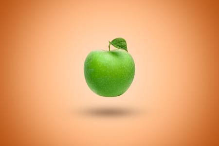Green apple on an orange background. Artistic background.