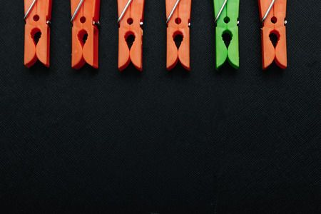 One green, linen clothespin in a row of orange, linen clothespins on a black background. Creative image, background. The concept is not like everyone else, an outcast, another.