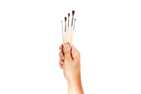 Many brushes in a male hand isolated on a white background. Banco de Imagens - 122718513