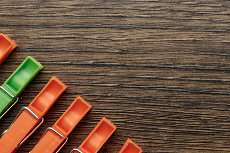 One green, linen clothespin in a row of orange, linen clothespins on a wooden background. Creative image, background. The concept is not like everyone else, an outcast, another.