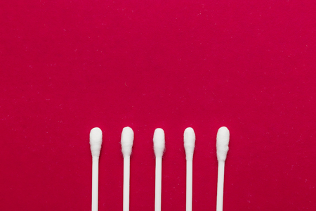 Hygienic, cotton buds on a red background. The concept of hygiene, cleanliness.