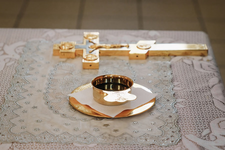 Silver, golden cup of wine on the table in church. Communion. Close up. Zdjęcie Seryjne