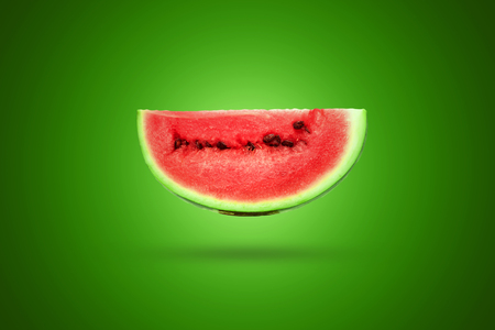 Slice of watermelon on a green background. Artistic background.