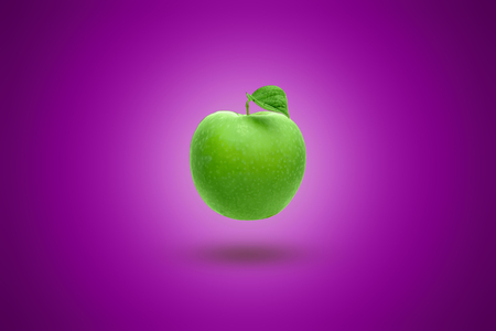 Green apple on a purple background. Artistic background. 写真素材