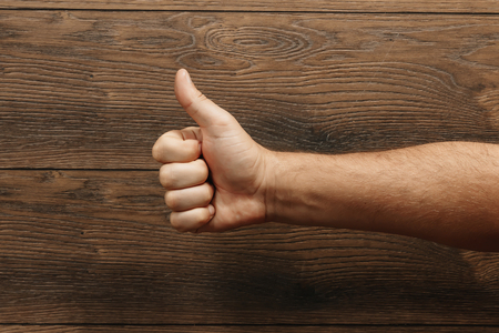 A mans hand shows a thumbs up on a wooden brown background. 스톡 콘텐츠