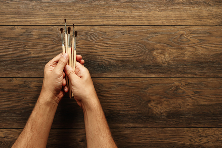 Male hands hold tassels on a brown wooden background. Close-up, top view. The concept of creativity, drawing. Copy space.