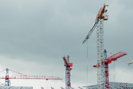 many construction cranes on blue sky - construction site