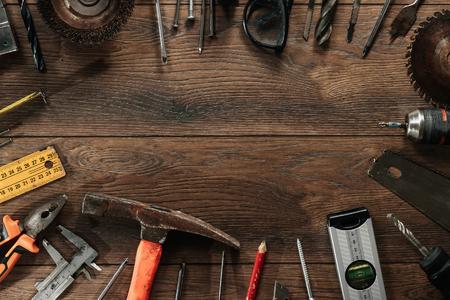 Una herramienta de construcción sobre un fondo de madera marrón. Vista desde arriba. Fondo de imagen, salvapantallas. El concepto de construcción, reparación, construcción, producción, diseño. Copie el espacio.