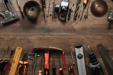 A construction tool on a brown wooden background. View from above. Picture background, screensaver. The concept of construction, repair, construction, production, design. Copy space. Foto de archivo