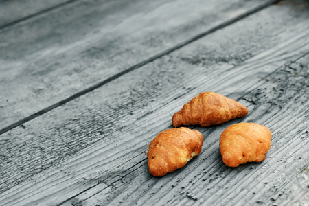 Fresh baked croissants on a wooden gray background. Copy space. The concept of a good morning, breakfast.