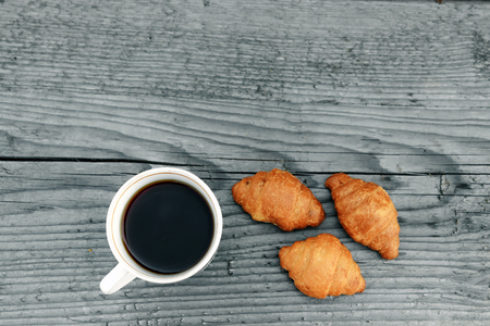 Fresh baked croissants on a wooden gray background. Imagens