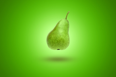 Green pear on a green background. Artistic background. Imagens