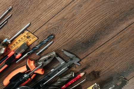 A construction tool on a brown wooden background. View from above. Picture background, screensaver. The concept of construction, repair, construction, production, design. Copy space. Imagens