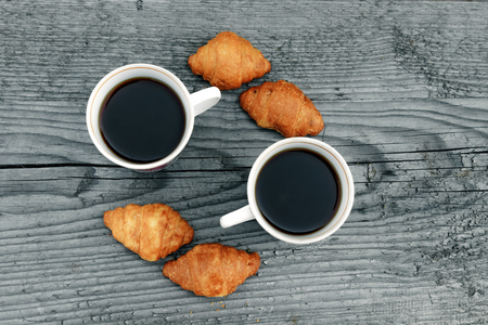 Coffee cups and fresh baked croissants on a wooden gray background. View from above.