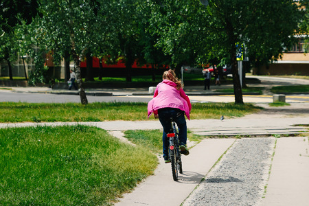Girl with a guy riding in a park on a bicycle Imagens