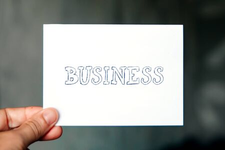 Concept of business, Business word written on white paper in a mans hand
