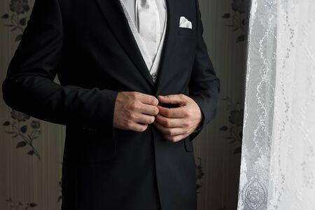 Un hombre con un traje azul se endereza las mangas