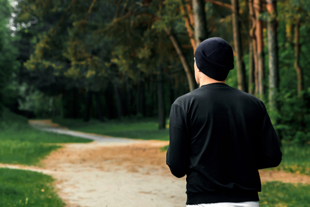 Morning jog in the park, a man in a black sports suit running around the park copy space Imagens