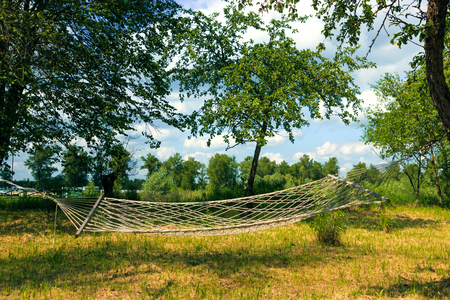 Relaxing lazy time with hammock in the green forest. Beautiful landscape with swinging hammock in the summer garden, sunny day outdoors. Travel, adventure, camping gear, nature outdoors items.