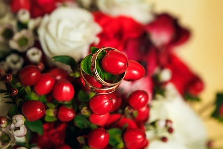 Golden wedding rings on the background of a wedding bouquet of red roses