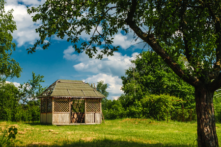 Outdoor wooden gazebo with roses and summer landscape background Stock Photo