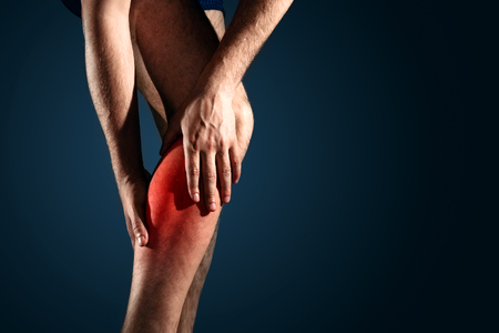 Pain in calf muscle pain in the leg, red pain on a blue background, leg of a man on a blue background close-up Stock Photo