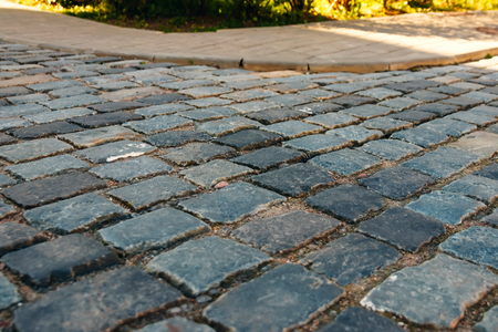Cobbled stone road shown at a small angle, reflection of light seen on the road
