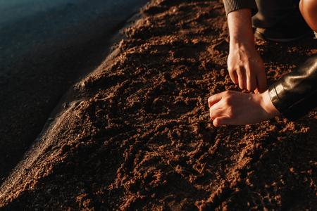 A loving couple draws a heart on the sand on the beach