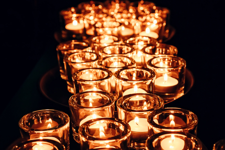 Romantic atmosphere, many small, lit candles on the table. Dark background.