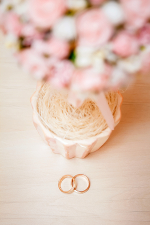 Gold wedding rings lie on a wooden table Banque d'images - 122988863