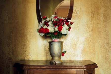 Beautiful wedding bouquet in a vase on a background of golden wall 版權商用圖片