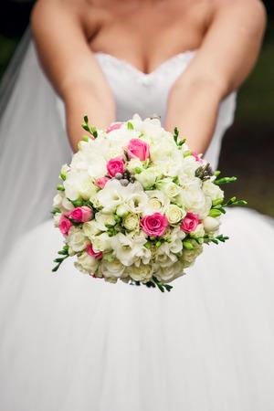 La novia sostiene un ramo de novia en sus manos en la naturaleza