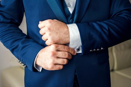 Un homme en costume bleu redresse ses manches