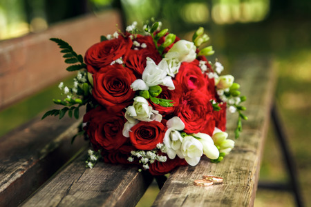 Gold wedding rings on a wooden bench on the background of a beautiful wedding bouquet