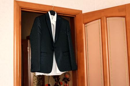 Jacket, tie and shirt hanging white walls, brown door