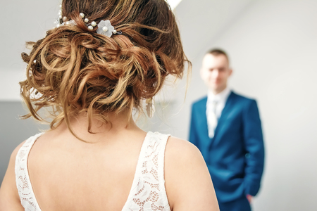 Bride standing with her back to the camera looking at the groom in the defocus Imagens
