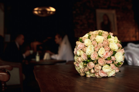 Golden wedding rings on the background of a wedding bouquet of red roses Banque d'images - 122994140